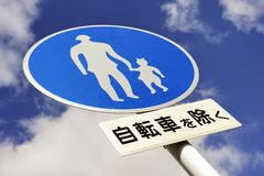 Traffic sign for pedestrian only route. Against beautiful sky,with Japanese text stock image