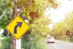 Traffic sign placed beside along the road on route twisty winding slope. background driver car. Reduce speed and use a lower gear on country road royalty free stock photos