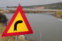 Traffic sign pointing right to a canal ! Stock Images