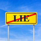 Traffic sign prohibiting lying. Yellow traffic sign prohibiting lying with the word - Lie - crossed through in red against a clear sunny blue sky in a conceptual Royalty Free Stock Photography
