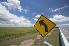 Traffic sign on road. Curved road traffic sign om the road with white cloud and blue sky background Stock Photography