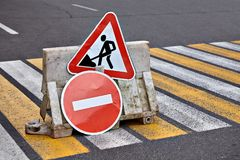 Traffic sign of road work and fence on zebra crossing. Street signs with simbol of road construction works and traffic forbidden access on pedestrian crossing Royalty Free Stock Photos