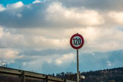 Traffic sign which means 120 kilometers per hour. Traffic sign.  Speed limit of 120 kilometers per hour. Blue sky and clouds Royalty Free Stock Images