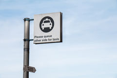 Traffic Sign: Taxi Logo. Please Queue Other Side for Taxis in Blue Sky royalty free stock image
