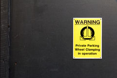 Traffic Sign: Warning - Private Parking. Wheel Clamping in Operation on Black Concrete Wall background royalty free stock image