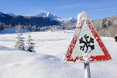 Traffic sign warns of snow and ice at winter Royalty Free Stock Image