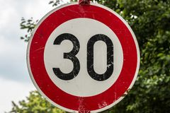 Traffic sign which means 30 kilometers per hour. Near by the street stock photography