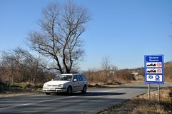 Traffic sign and white car at the entrance to the Republic of Kosovo from Serbia Stock Photos