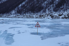 Traffic sign on winter road along the river. Royalty Free Stock Photography