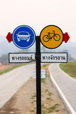 Traffic signboard with red arrow indicating: Car lane and Bicycl. Pair of round traffic signboard with red arrow indicating: Car lane and Bicycle lane Royalty Free Stock Images