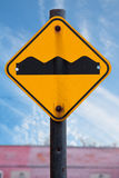 Traffic Signs. A bumpy road ahead sign on a rusty pole against a blue sky with wight clouds and a red building Royalty Free Stock Photo