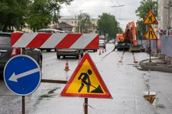 Traffic signs, detour, road repair on the background of the street and the excavator Royalty Free Stock Photos