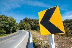 Traffic signs say the curve left direction on mountain highway,. Warning accident stock images