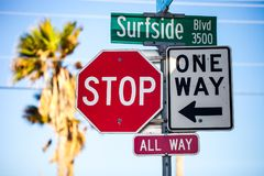 Traffic signs, stop all way and one way, and Surfside Blvd sign stock image