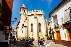 Traffic on the small street in Sevilla. Sevilla, SPAIN - September 09, 2015: Street in Sevilla in sunny summer day, motorcyclist at an intersection, pedestrians royalty free stock photo