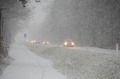 Traffic in snow. Sparce traffic moving slowly, on a road during heavy snowfall that causes reduced visibility Royalty Free Stock Images