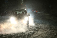 Traffic at snowfall. Cars driving on the road in the aggravated traffic due to strong snowfall Royalty Free Stock Photo