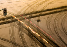 Traffic at snowy intersection. A view of vehicle or tire tracks in light snow at a busy traffic intersection at night Stock Photos