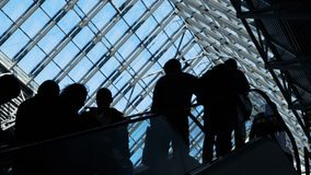Group of people silhouettes moving on escalator. Traffic of society and population to depart or meeting in public place or shopping store. Social symbol of stock footage
