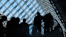 Group of people silhouettes moving on escalator. Traffic of society and population to depart or meeting in public place or shopping store timelapse. Social stock video