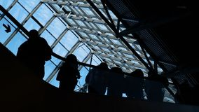 Group of people silhouettes moving on escalator. Traffic of society and population to depart or meeting in public place or store slowmotion. Social symbol of stock video footage