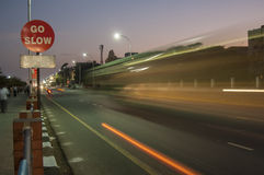 Traffic speeds past a go slow sign Royalty Free Stock Photography