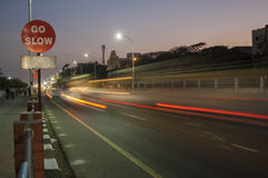 Traffic speeds past a go slow sign Royalty Free Stock Photos