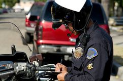 Traffic stop. A motorcycle police officer writing a ticket to a speeding driver Royalty Free Stock Image