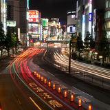 Traffic streams down a Tokyo street full of Neon Signs. Traffic streaks past neon signs in Tokyo. Just having rained, the road has a sheen of water reflecting Royalty Free Stock Photography