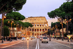 Traffic street in front of Colosseum, Rome, Italy. Rome, Italy - April 04: Traffic on the Via dei Fori Imperiali street in front of Colosseum in the evening Stock Photos