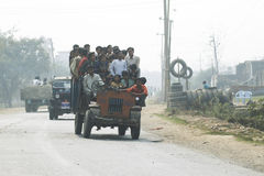 Traffic on streets of India. People crowded on a tractor taxi that is tilted due to heavy load stock images