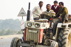 Traffic on streets of India. People crowded on a tractor that is tilted due to the bank on the road royalty free stock photography