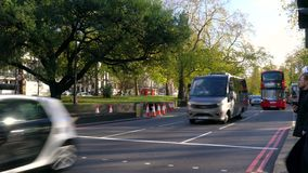 Traffic, taxis and red double decker London buses driving on Park Lane towards Marble Arch, Hyde Park, London stock video footage