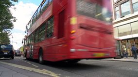 Traffic, taxis and red double decker London buses driving past Selfridges, Oxford Street, London, England stock video footage