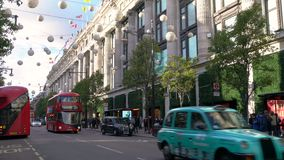 Traffic, taxis and red double decker London buses driving past Selfridges, Oxford Street, London, England stock video