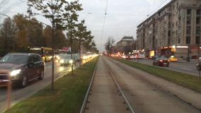 Traffic on tram tracks. The traffic on the tramways, the rails, shot through the rear window, a small green area to separate the tram tracks from a large number stock video footage