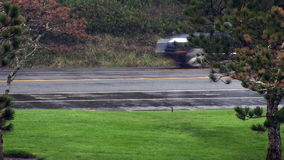 Traffic On Two Lane Road In Rain. Cars Going In Both Directions Seen Through Rain Past Trees And Grass stock video