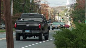 Traffic on two-lane road in town (1 of 3). A view or scene from around town stock footage