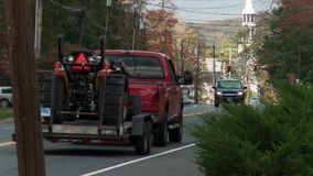 Traffic on two-lane road in town (3 of 3). A view or scene from around town stock footage