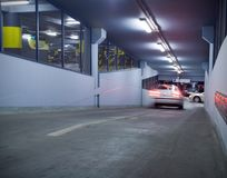Traffic in underground parking garage. Motion blur from moving car. Number plates and trademarks erased Royalty Free Stock Image