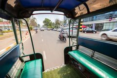 Traffic in Vientiane, Laos. View of traffic on a street from the back of a songthaew pick-up or small truck with benches along the sides in Vientiane, Laos, on a royalty free stock images