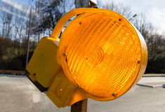 Traffic warning lamp in yellow on a street macro Royalty Free Stock Images