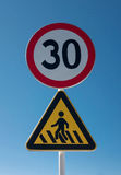 Traffic warning signs. Speed limit and crosswalk warning signs isolate on the blue sky Royalty Free Stock Photography