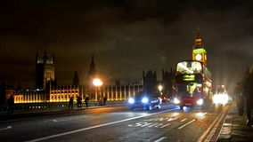 Traffic on Westminster Bridge in London. LONDON circa DEC: London red bus on Westminster bridge with Big Ben and House of Parlament at background at dramatic stock video footage