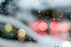 Traffic through wet glass and bokeh effect Stock Photos