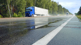 Traffic on wet road highway with mist splash. View from ground of traffic on wet road, highway with mist splash after rain with green trees on a roadside on Stock Photography