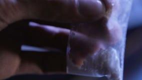 Trafficante di droga che tiene il sacchetto di plastica con la sostanza bianca, dipendenza a cocaina video d archivio