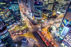 Traffichi le velocità attraverso un'intersezione alla notte in Gangnam, Seoul in Corea del Sud fotografia stock