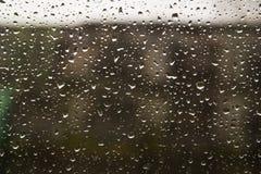 Traffichi nel giorno piovoso con la vista della strada attraverso la finestra di automobile con le gocce di pioggia Immagini Stock