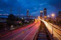 Traffichi sulla strada di città attraverso le costruzioni moderne a penombra in Tailandia Immagini Stock